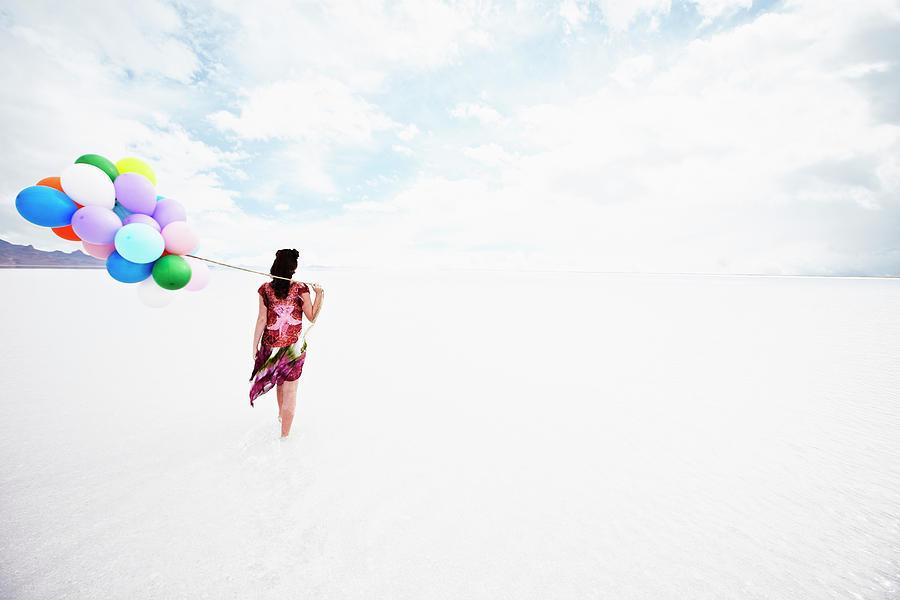 Woman Holding Balloons Walking Through Photograph by Thomas Barwick