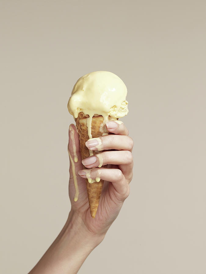 Woman Holding Melting Ice Cream Cone Photograph by Walker And Walker