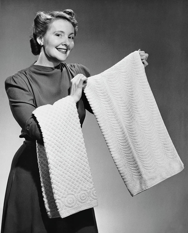Woman Holding Up Towels Photograph by George Marks