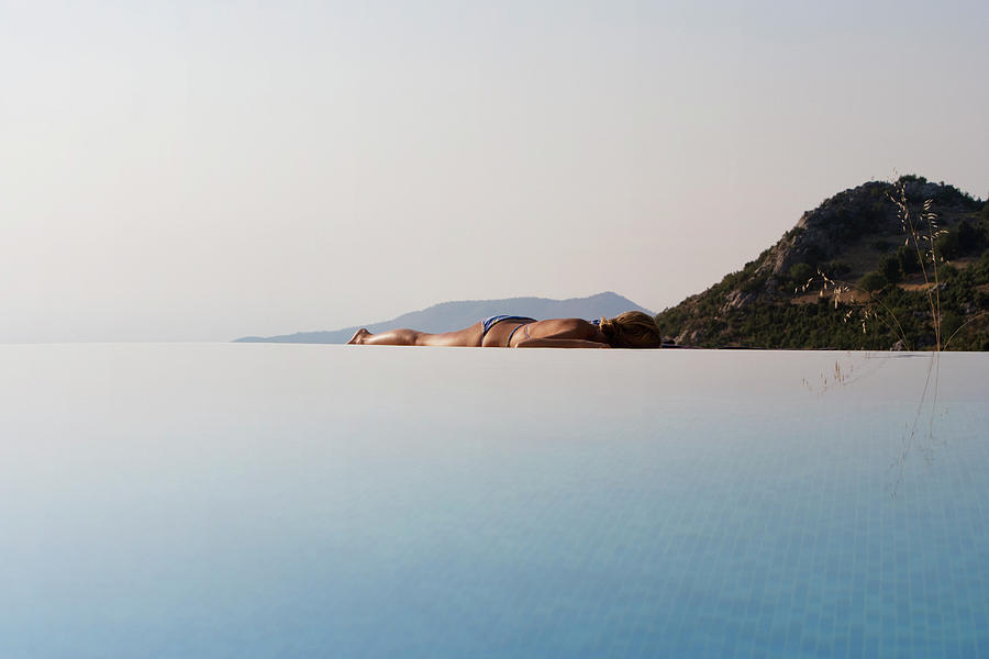 Woman Laying On Edge Of Infinity Pool Photograph by J.a. Bracchi