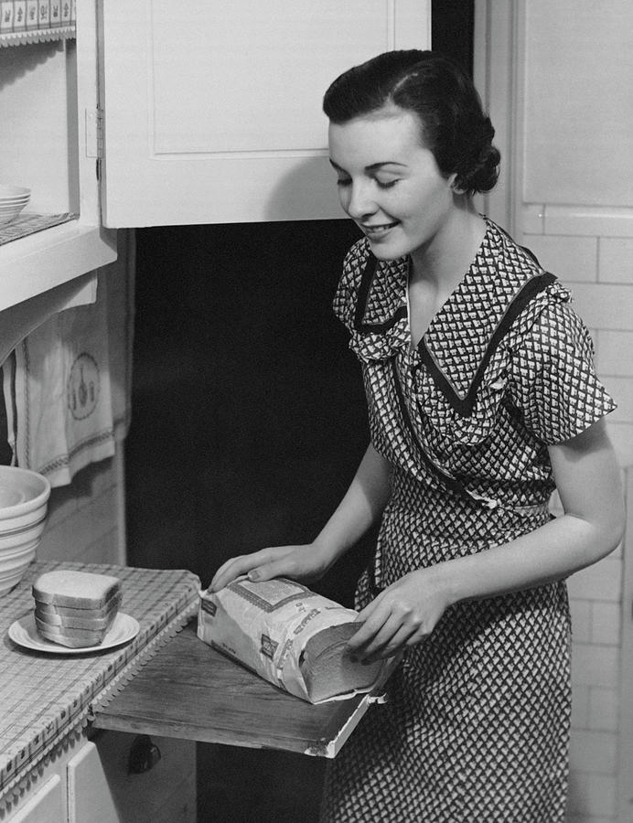 Woman Placing Bread On Plate Photograph by George Marks