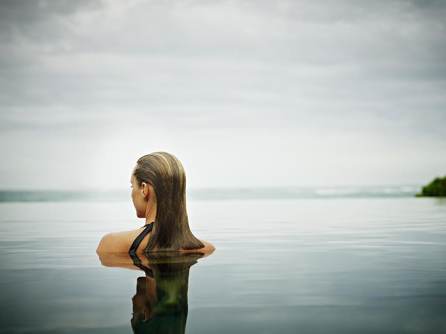 Woman Standing In Infinity Pool Photograph by Thomas Barwick