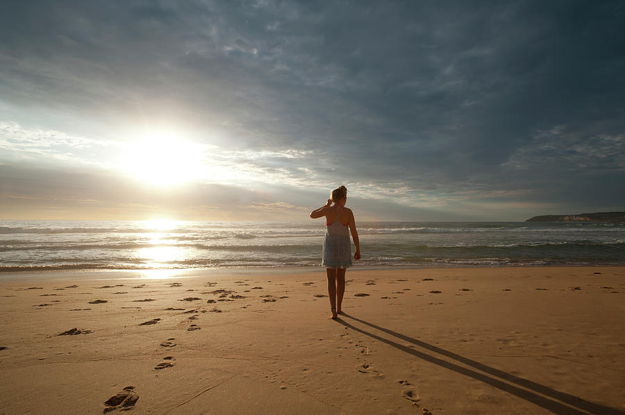 Woman Walking Along The Beach Photograph by Courtneyk