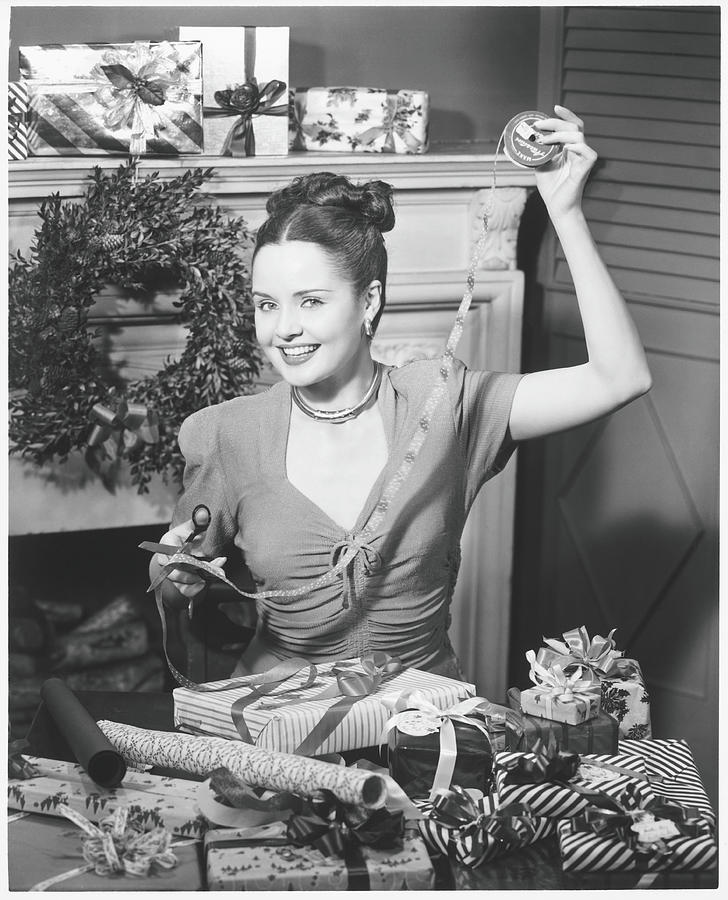 Woman Wrapping Christmas Presents In Photograph by George Marks