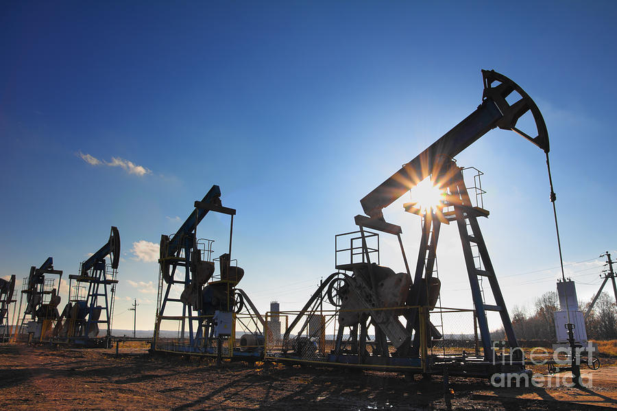 Steel Photograph - Working Oil Pumps Silhouette Against Sun by Kokhanchikov