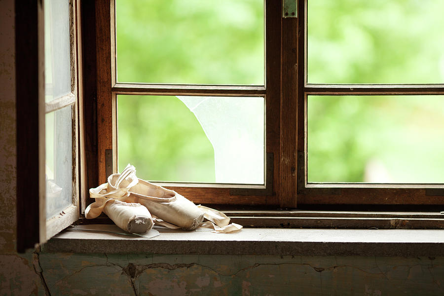 Worn Out  Ballet Shoes Lie On The Old Photograph by Miljko