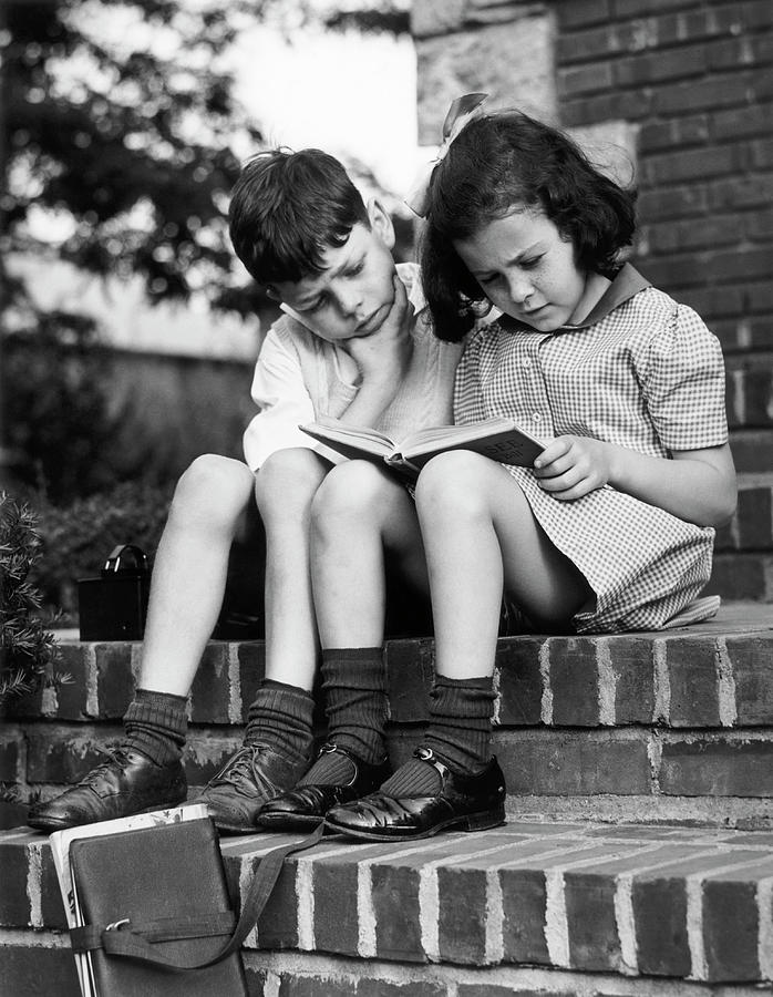 Young Boy & Girl Reading A Book Outdoors Photograph by George Marks