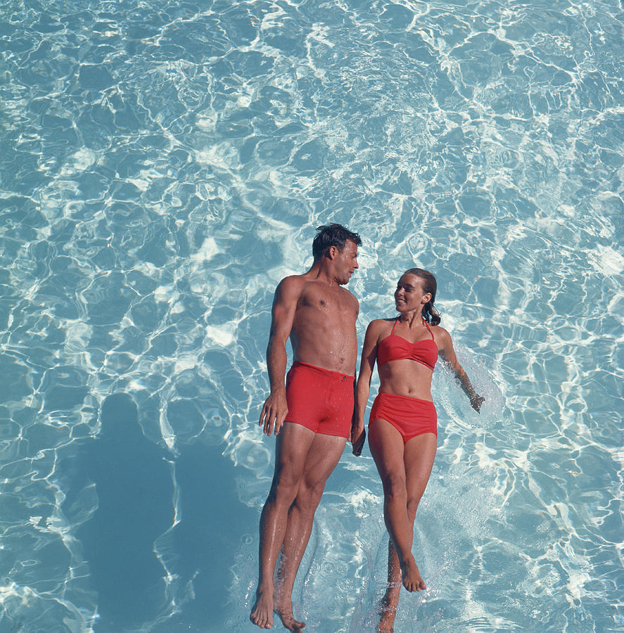 Young Couple Jumping In Swimming Pool Photograph by Tom Kelley Archive