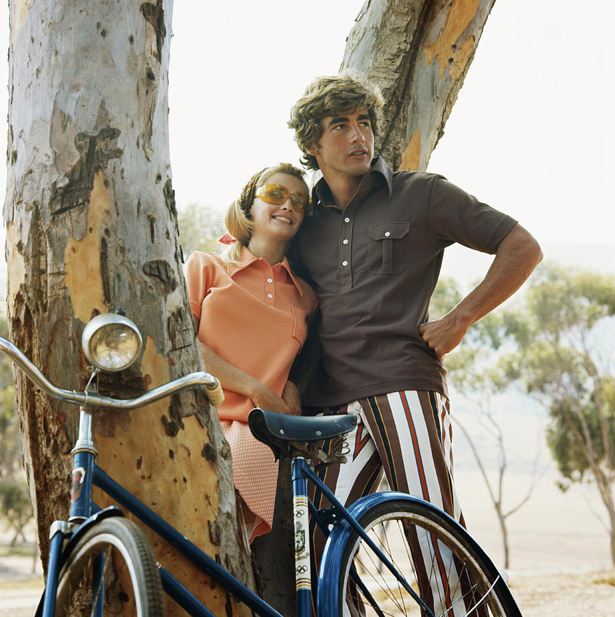 Young Couple Leaning On Tree With Photograph by Tom Kelley Archive