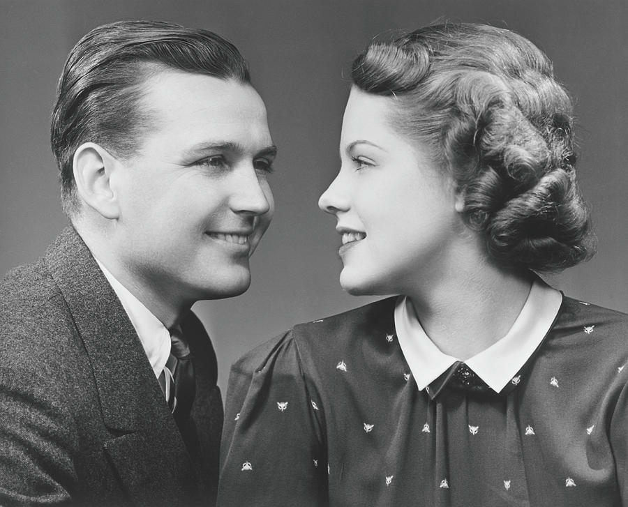 Young Couple Looking In Eyes In Studio Photograph by George Marks