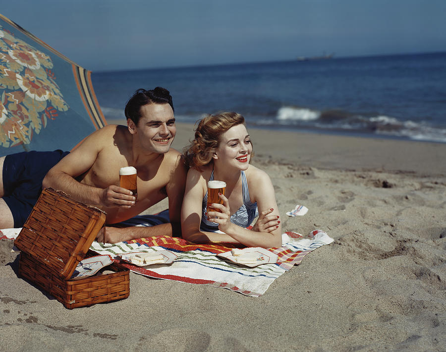 Young Couple Lying On Beach With Beer Photograph by Tom Kelley Archive