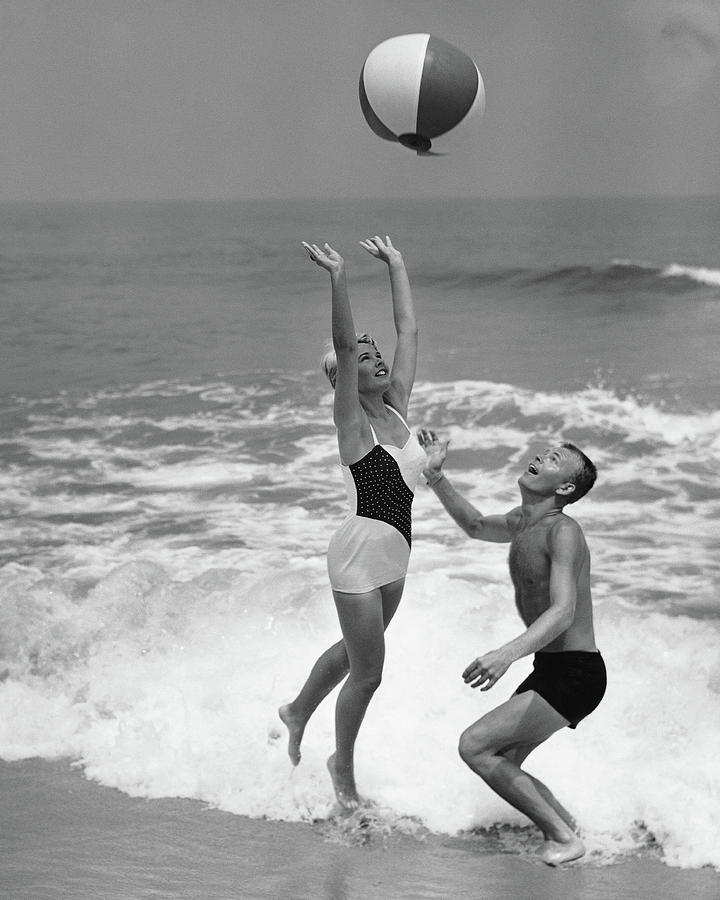 Young Couple Playing With Beach Ball At Photograph by Stockbyte