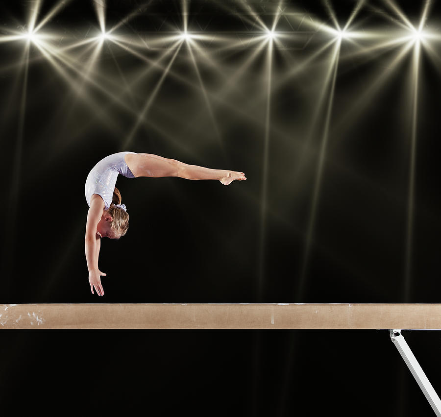 Young Female Gymnast On Balance Beam Photograph by Robert Decelis Ltd