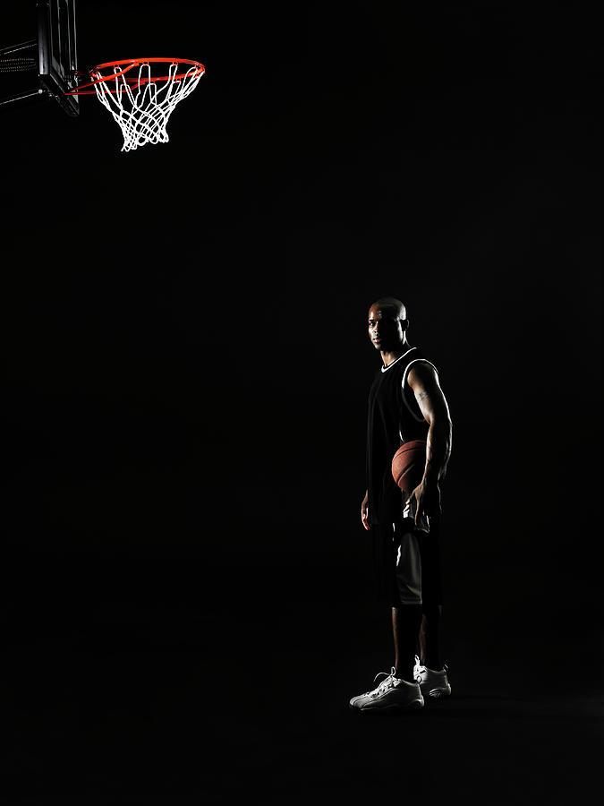 Young Man Holding Basketball Beneath Photograph by Thomas Barwick