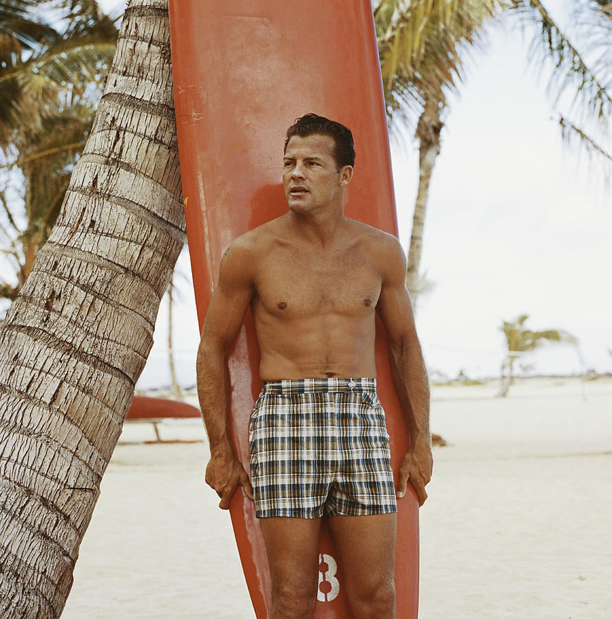 Young Man Holding Surfboard On Beach Photograph by Tom Kelley Archive