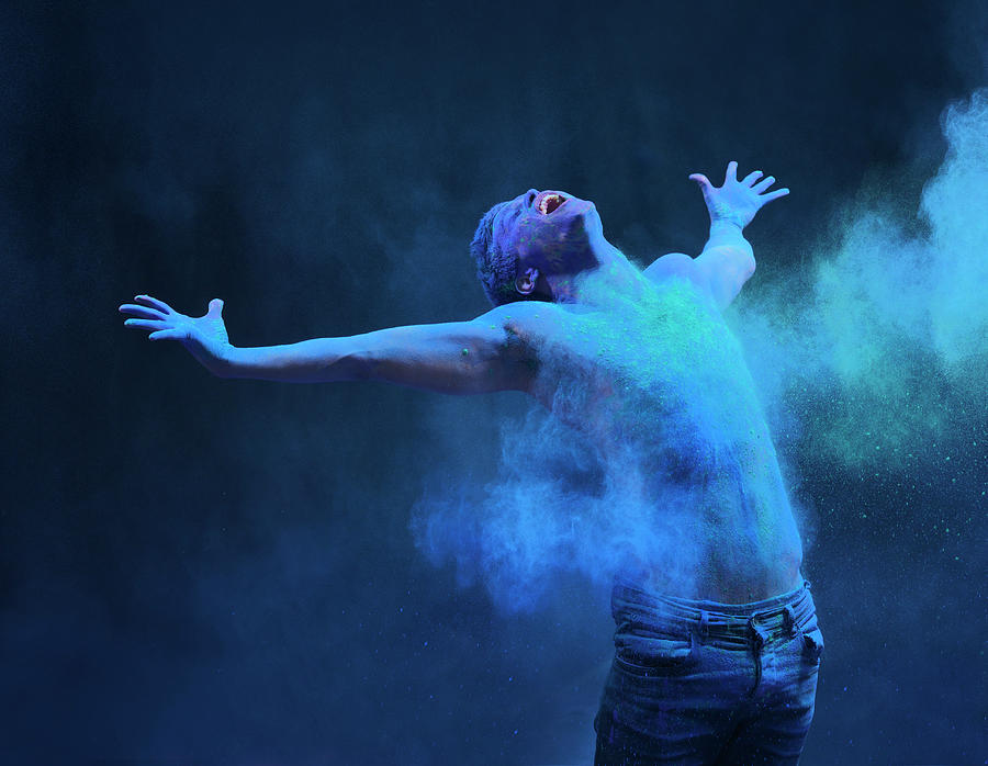 Young Man In Spray Of Colored Powder Photograph by Henrik Sorensen