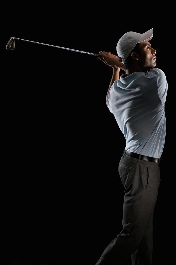 Young Man Swinging A Golf Club Photograph by Pm Images