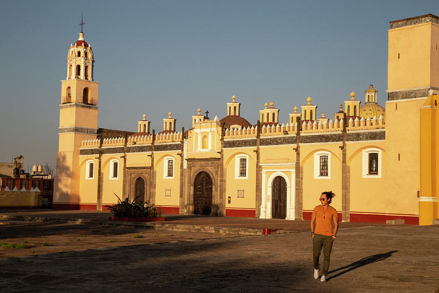 Capilla Real Photograph - Young Mexican Man Walking In Front Of Yellow Church In Cholula, Puebla by Cavan Images