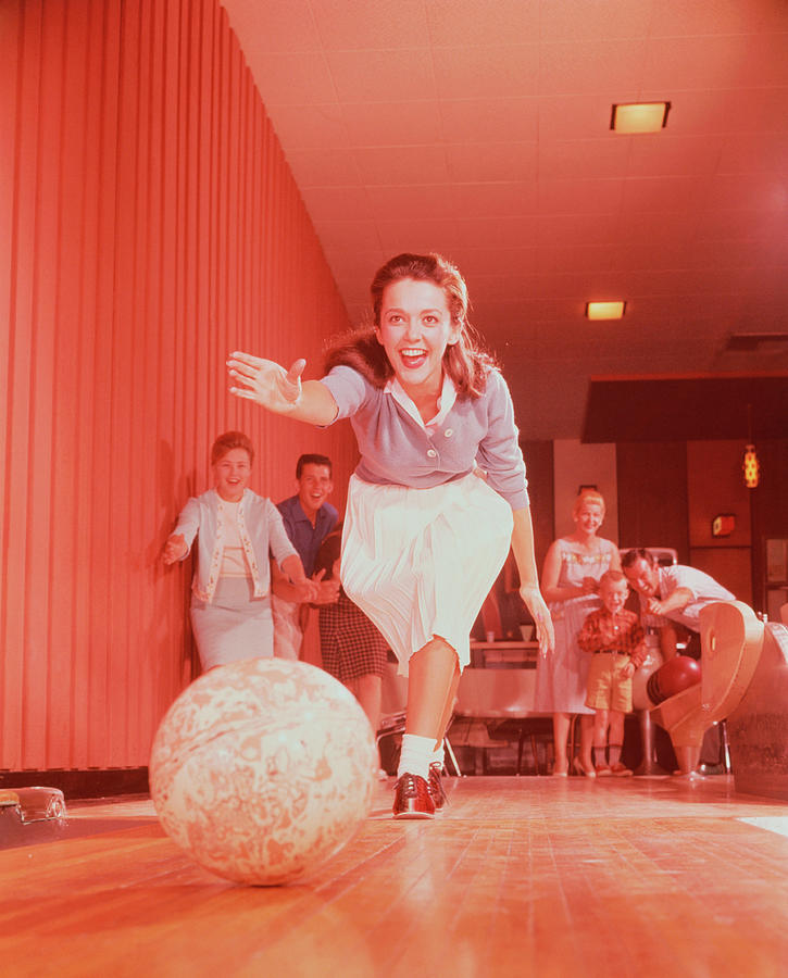 Young Woman Bowling, Family Watching In Photograph by Fpg