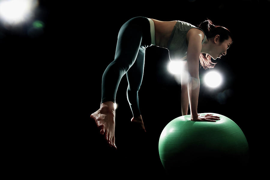 Young Woman Exercising With Fitness Ball Photograph by Runphoto