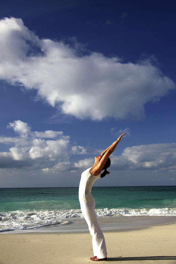 Young Woman Stretching On A Beach Photograph by Elke Selzle