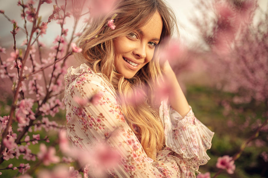 Amazing young woman posing in apricot tree orchard at spring Photograph by Miljko