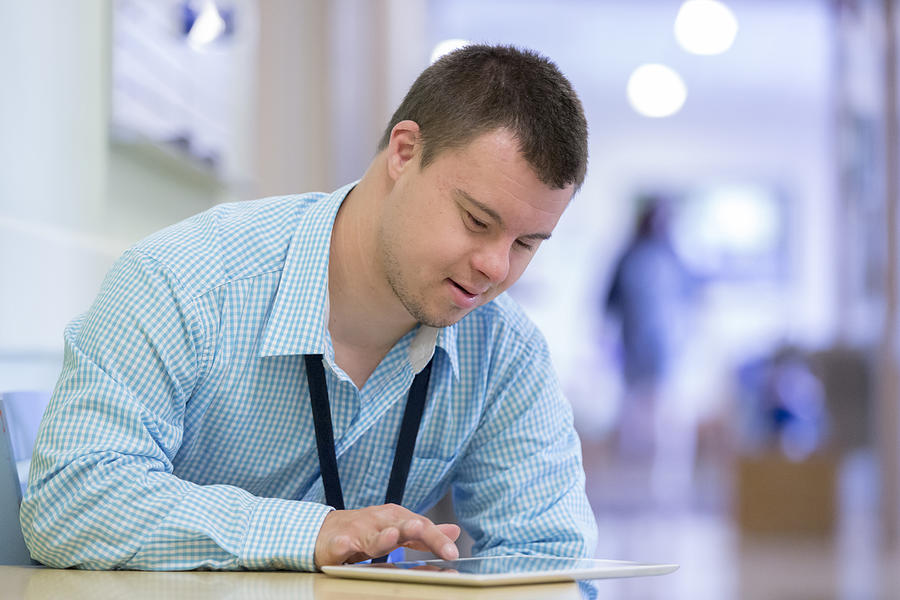 Caucasian man with Down Syndrome using digital tablet in hospital Photograph by Disability Images