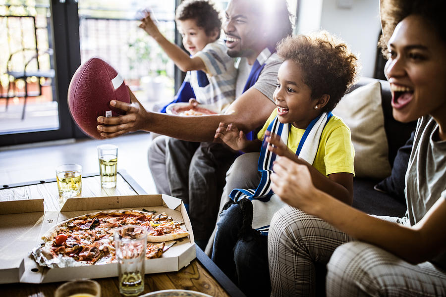 Cheerful black family cheering while watching rugby match on TV at home. Photograph by Skynesher