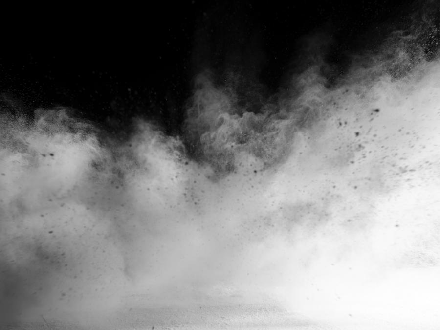 Explosion by an impact of a cloud of particles of powder and smoke of color white on a black background. Photograph by Jose A. Bernat Bacete
