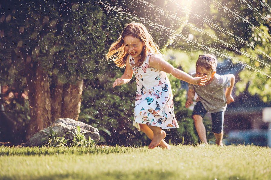 Happy kids playing with garden sprinkler Photograph by Lisegagne