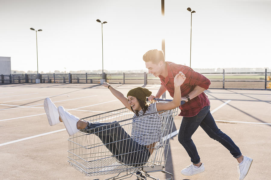 Playful young couple with shopping cart on parking level Photograph by Westend61