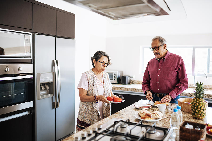 Senior married couple eating healthy food for breakfast. Photograph by Drazen_