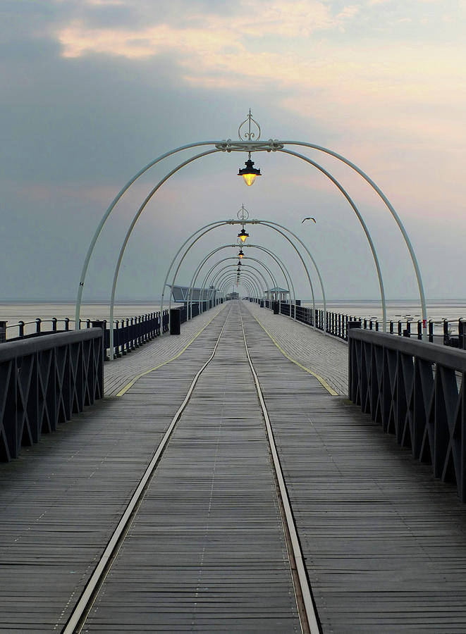 southport pier at sunset with walkway and tram lines by Philip Openshaw