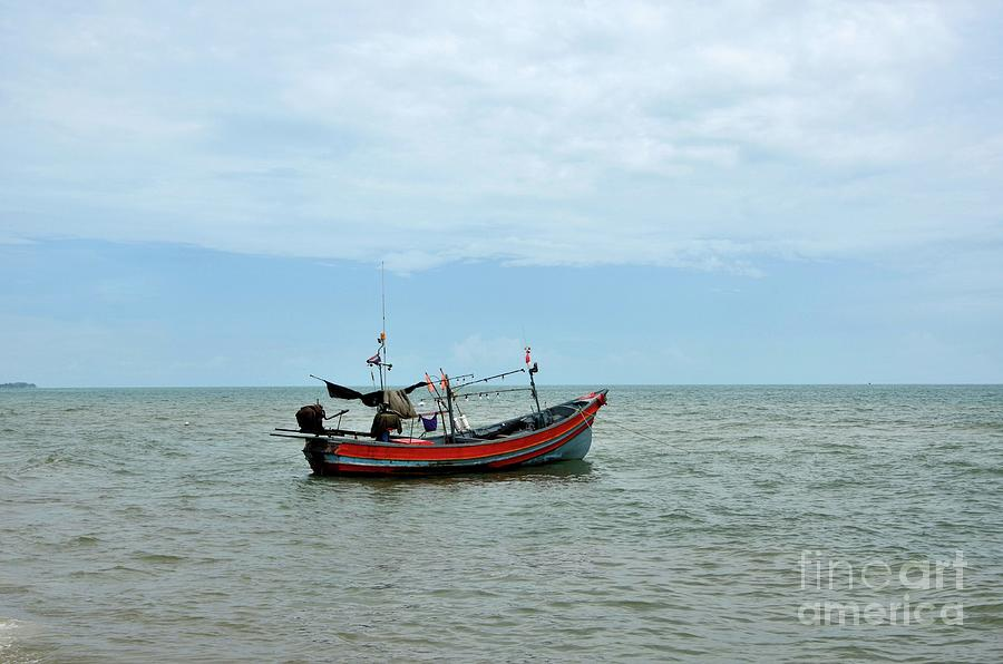 Thai fishing boat with motor parked at sea by beach in Pattani fishing village Thailand by Imran Ahmed