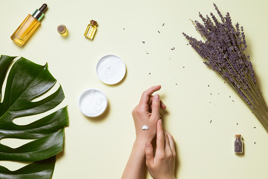 Top view and flat lay of woman holding cream on hands over white table with cosmetic products - avocado oil, cream and bamboo Photograph by Amax Photo