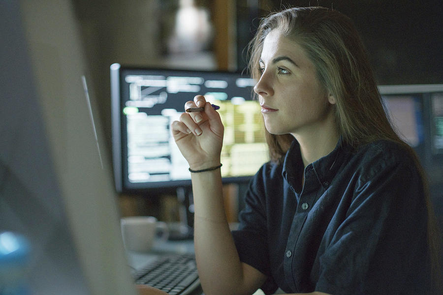 Woman monitors dark office Photograph by Laurence Dutton
