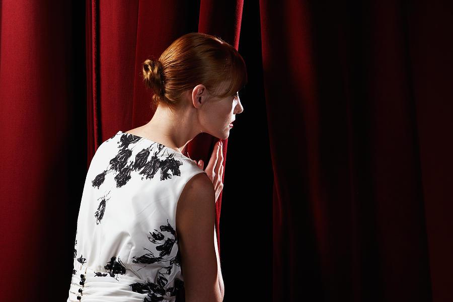 Young woman peeking through stage curtain Photograph by Leonard Mc Lane