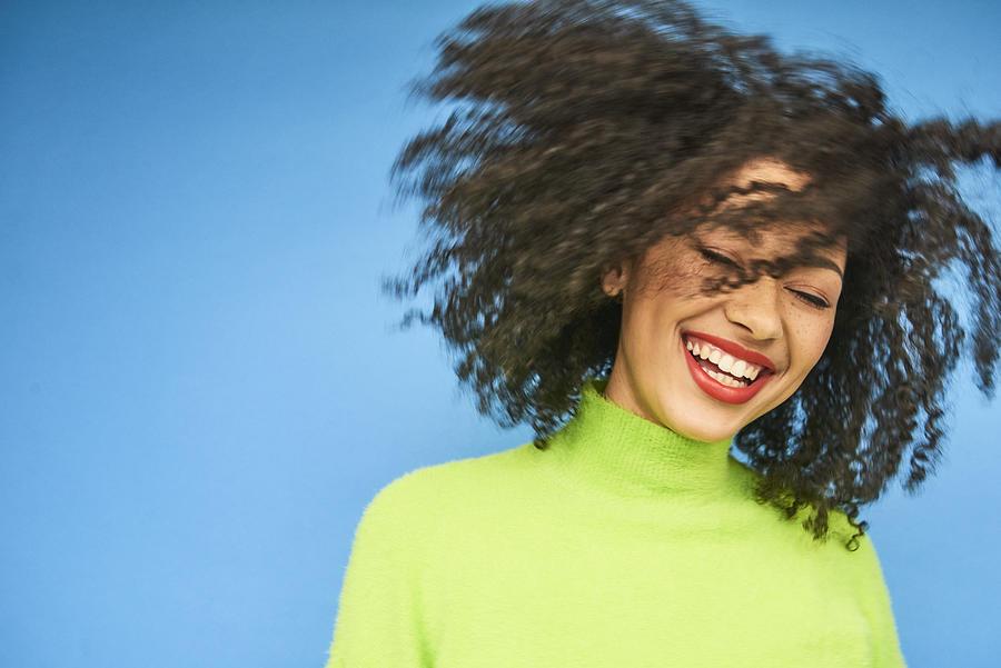 Colourful studio portrait of a young woman dancing Photograph by Flashpop