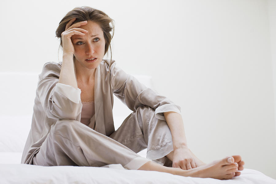 Depressed woman in pajamas sitting in bed Photograph by Tom Merton