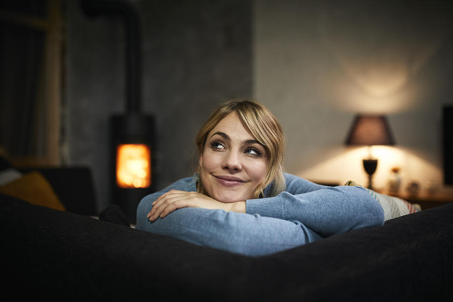 Portrait of smiling woman relaxing on couch at home in the evening Photograph by Westend61