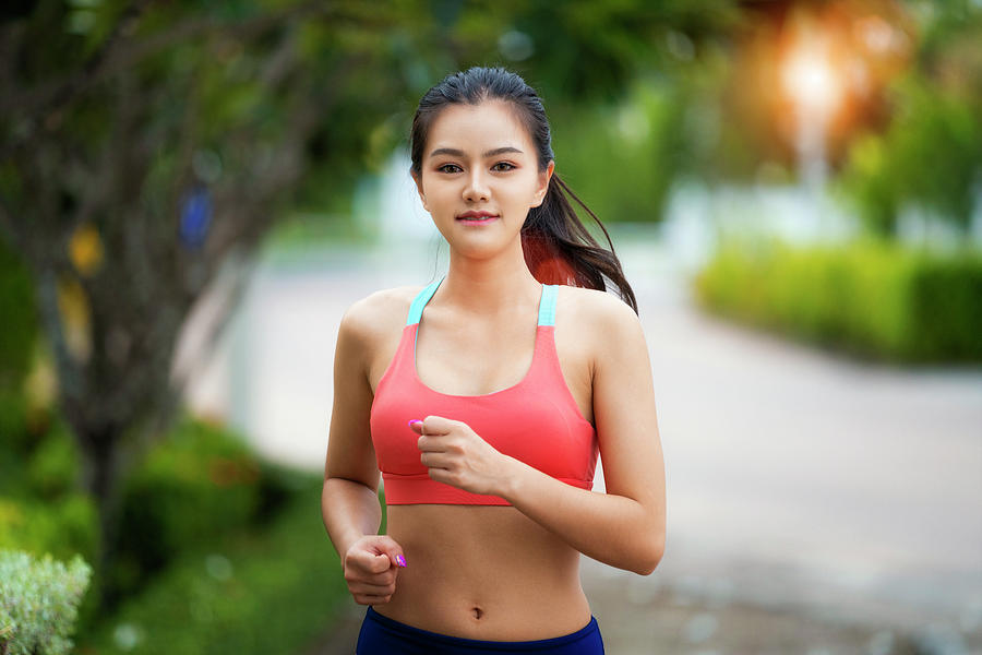 Asian girl running in the Park and doing exercises Jogging Photograph by  Anek Suwannaphoom