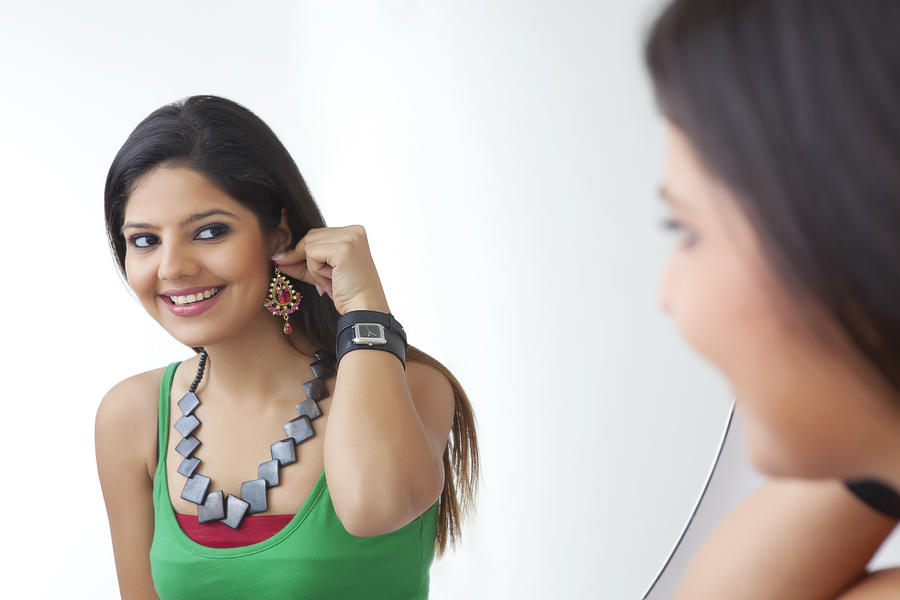 Young woman looking at herself in the mirror Photograph by Ravi Ranjan