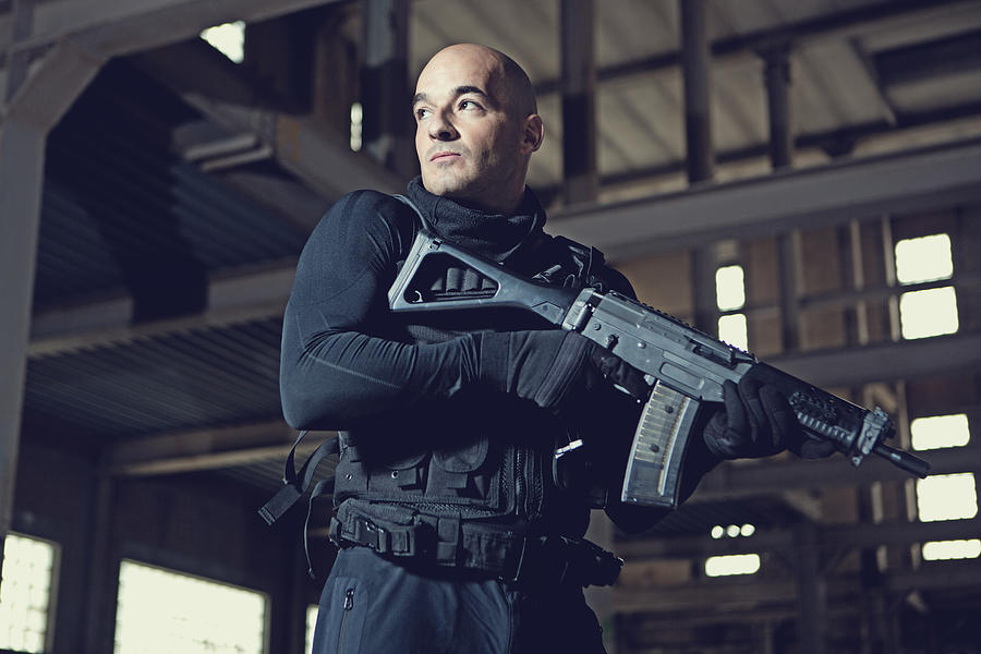 Male military swat team member holding gun in abandoned warehouse Photograph by Lorado