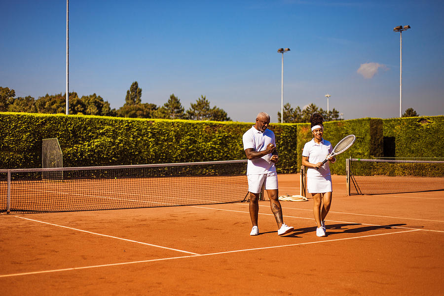 A beautiful black female tennis player on the court with her father and coach Photograph by Lorado