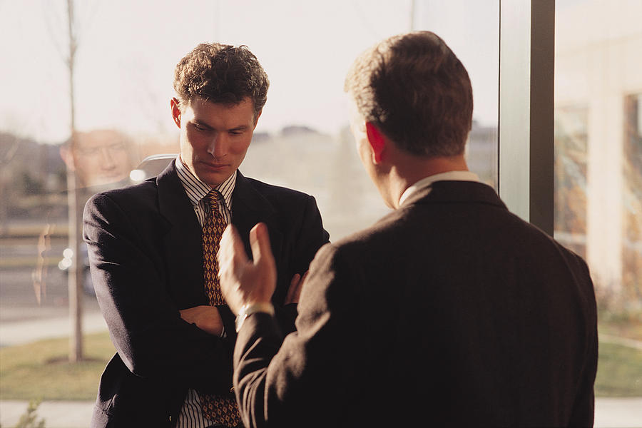 A business executive dressed in a suit confronts an employee and uses hand gestures as he talks Photograph by Photodisc