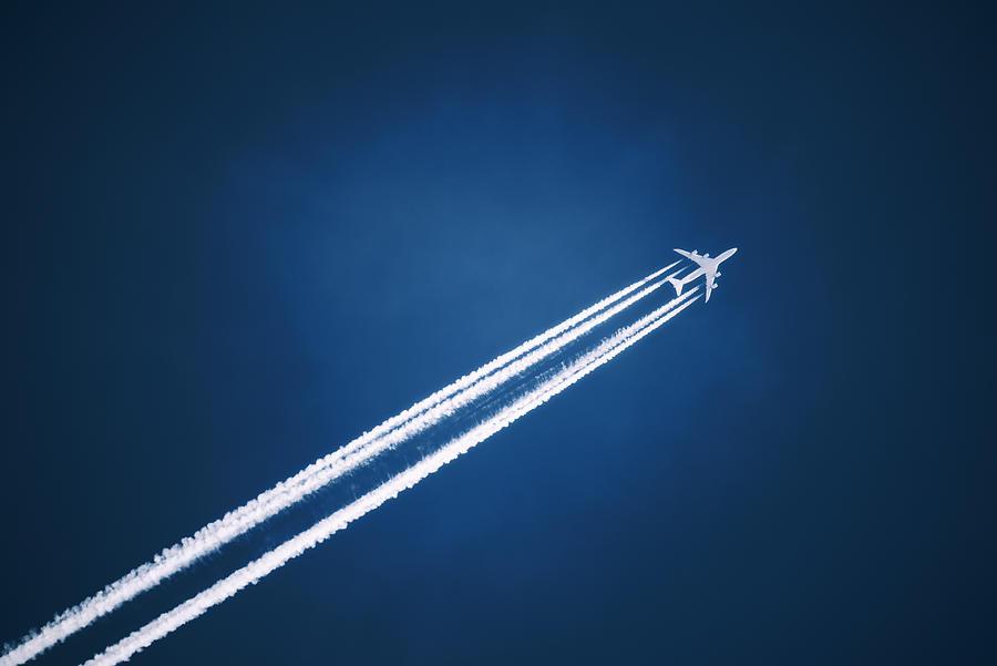A Jet Vapour Trail Across A Dark Blue Sky. Photograph by Mint Images