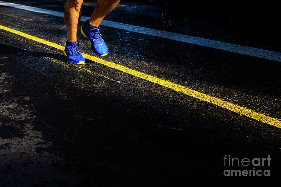 A lonely runner trains on wet asphalt at sunset, copy space. by Joaquin Corbalan