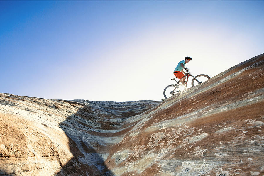 A man riding a mountain bike on an extreme sandstone ledge Photograph by Robb Reece