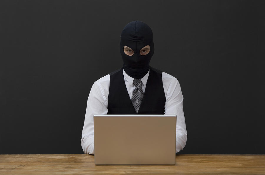 A man wearing a  balaclava and using a laptop Photograph by Andreas Schlegel