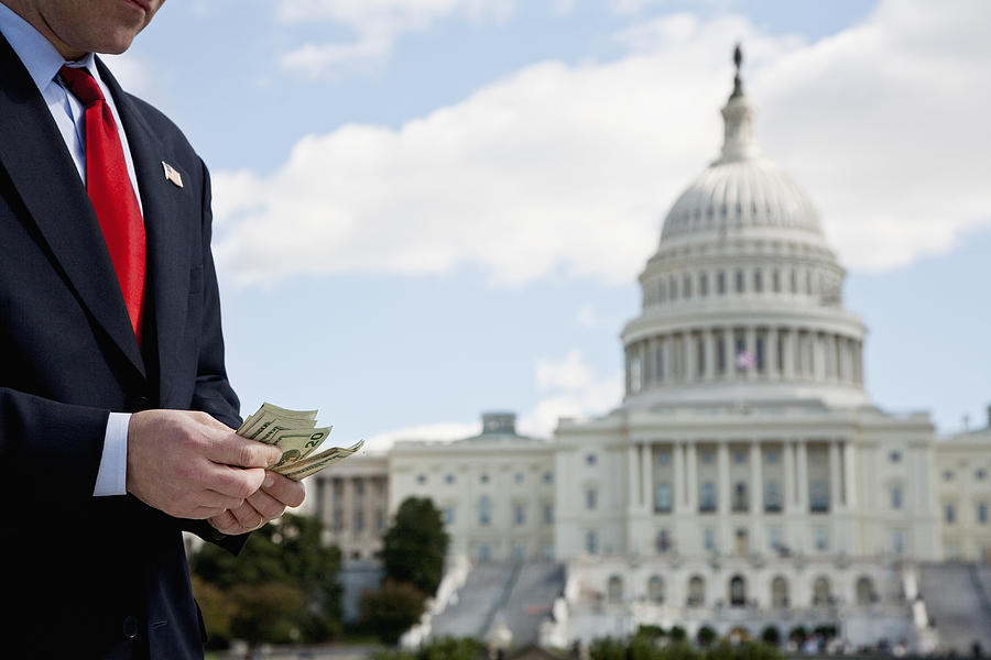 A politician counting money in front of the US Capitol Building Photograph by fStop Images - Antenna